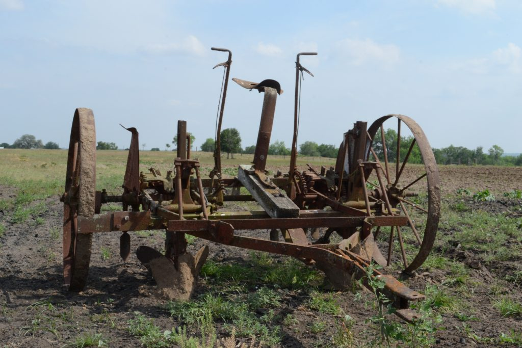 old rusted plow in field